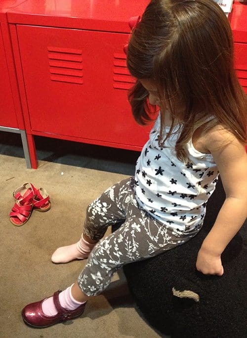 Toddler in a while tank top with stars and floral leggings trying on a pair of shoes