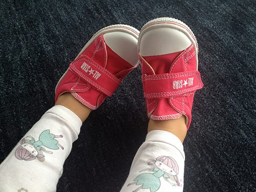 Red velcro Converse on the feet of a toddler
