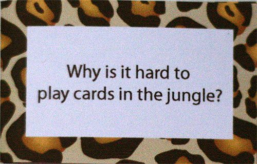 """Why is it hard to play cards in the jungle"" (close up shot of a joke printed on cheetah patterned paper)"