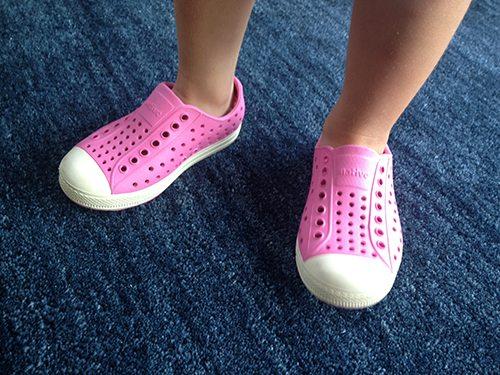 Small feet wearing pink Crocs