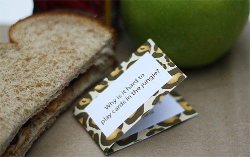 A small card with a joke printed on it laying next to a sandwich and a green apple