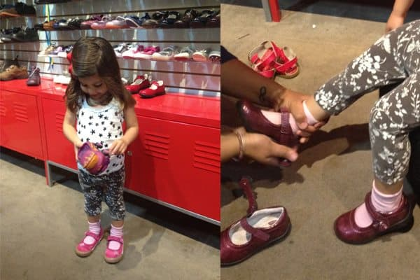 Little girl trying on pink shoes
