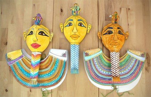 Three different mummy mask costumes all colored in and cut out laying on a wooden table