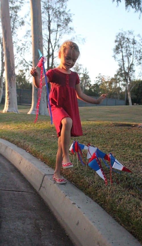 A girl holding parade pennant while walking on a curb