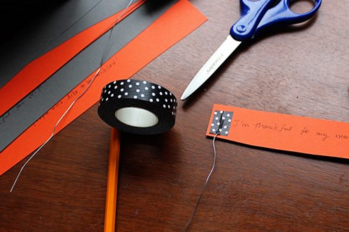 taping wire to secret messages on paper with Washi tape