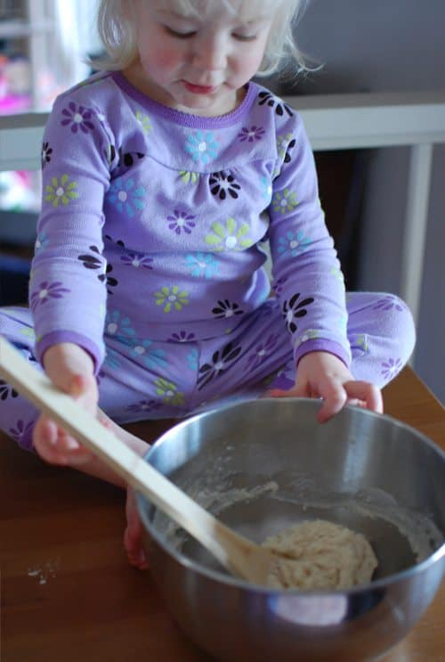 Child sitting on a counter top mixing dough