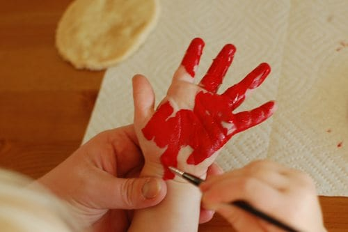 Painting a child's hand with red paint