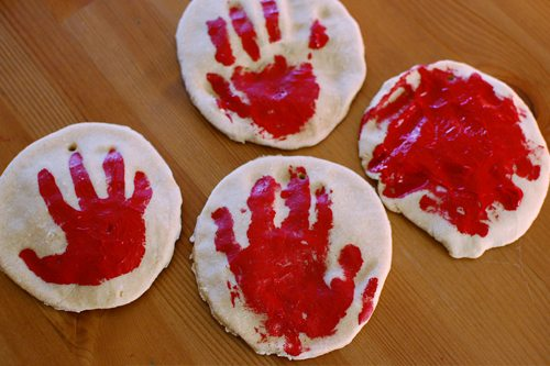 Four salt dough ornaments with red hand prints