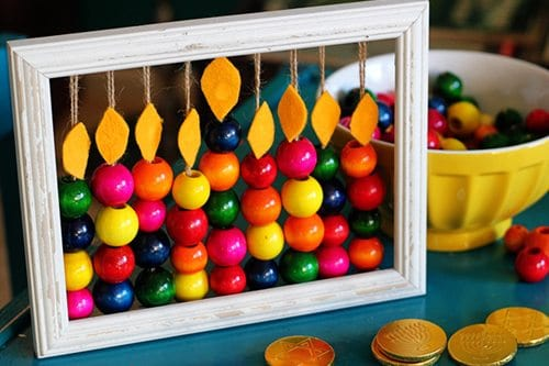 DIY Abacus Menorah next to bowl of beads on a table