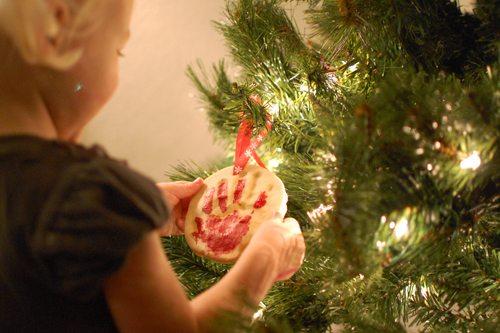 Child hanging salt dough ornament on Christmas tree