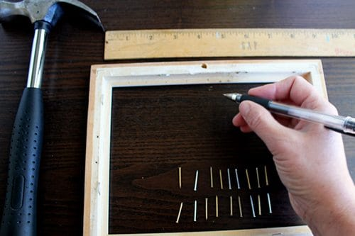 A table with hammer nails ruler and wooden frame