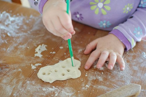 Child's hand making holes in dough with green stick