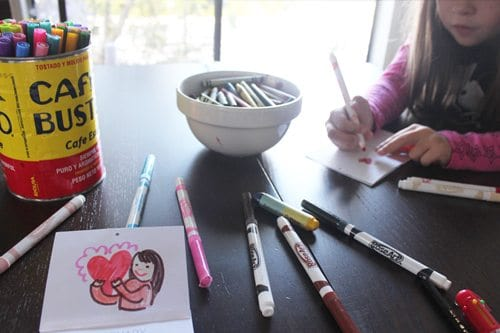 table with markers laying on it and a child coloring