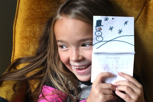 smiling child holding up mini calendar page