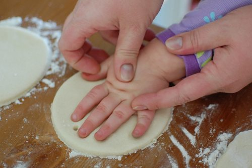 Putting child's hand imprint onto rolled out salt dough