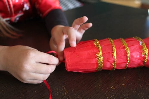 child tying ribbon into a knot