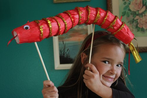 Child holding Year of the Snake Puppet