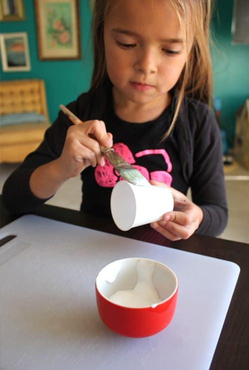 child painting glue onto a plastic cup
