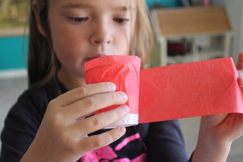 child wrapping red tissue paper onto a plastic cup