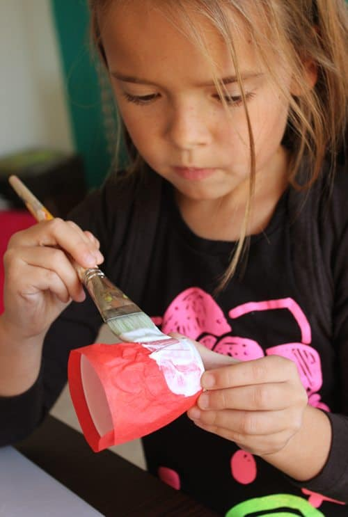 Child painting glue on top of red tissue paper on plastic cup