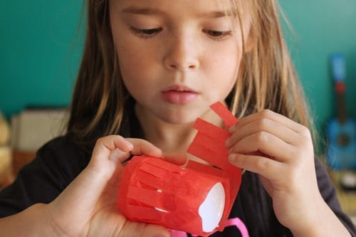 Child layering paper fringe on paper cup