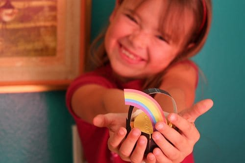 smiling child holding a paper pot of gold