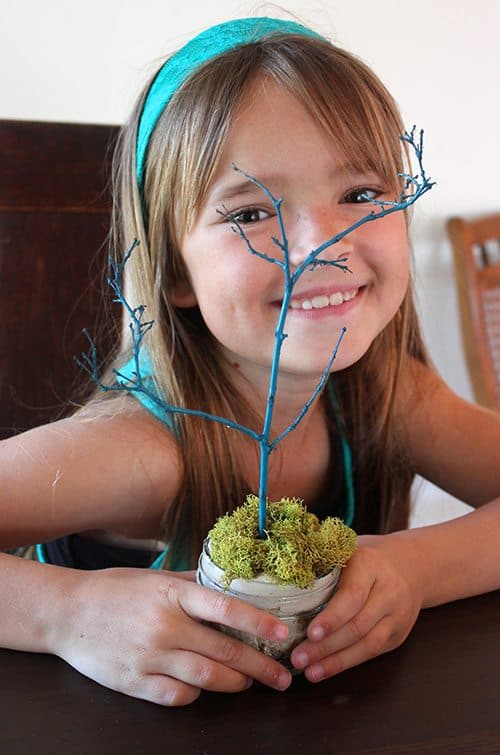 child showing off mini easter tree craft