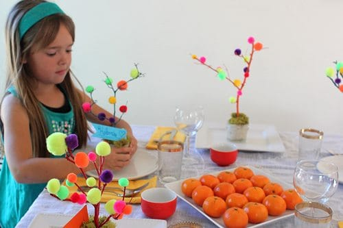 Child decorating table for Easter with mini trees crafts