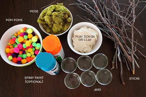 supplies for DIY mini Easter trees craft (pom poms, moss, spray paint, clay, jars, sticks)
