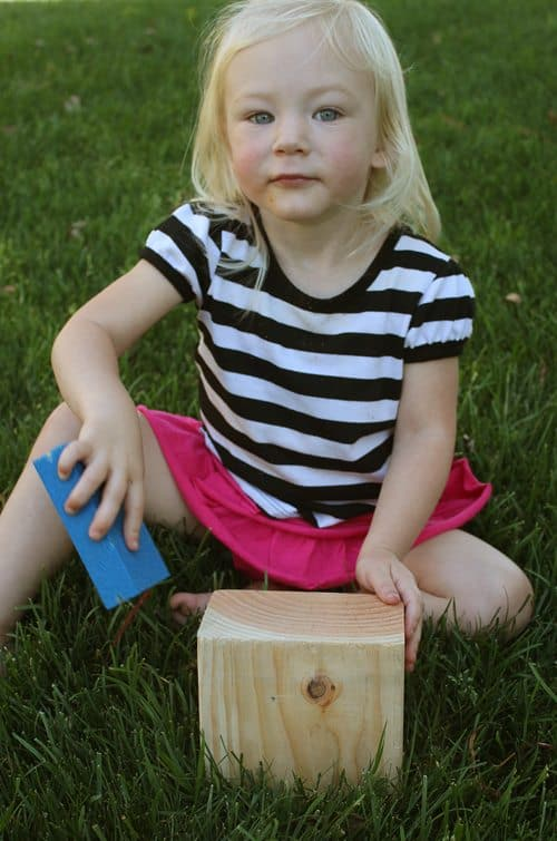 Child sitting in grass sanding a wooden block