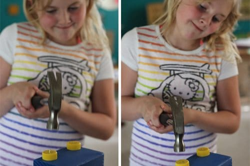 Child hammering nails through bottle caps for wheels on wooden block