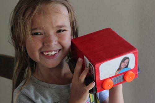 Smiling child holding up photo cube craft
