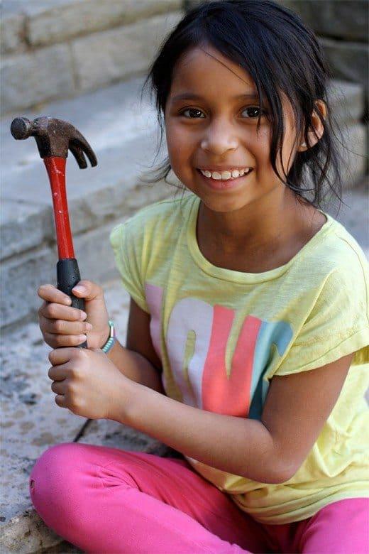 A girl holding a hammer