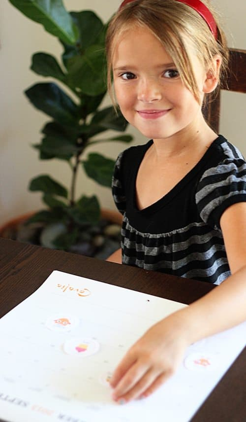 a young girl putting stickers on a calendar