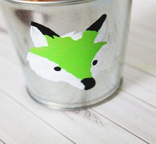 child's painting of a green and white fox on a metal bucket