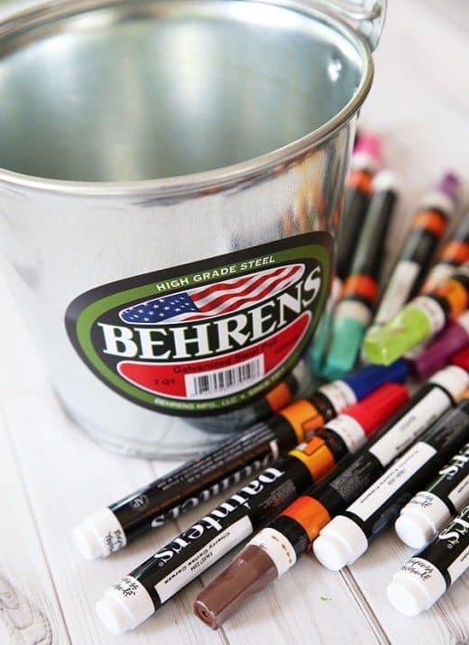 A bunch of markers laying next to a metal bucket