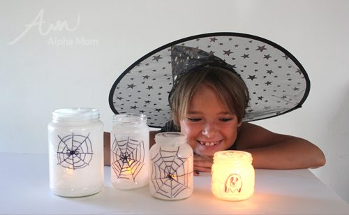 4 spiderweb candle holders on a table being admired by a young girl in a witch's hat