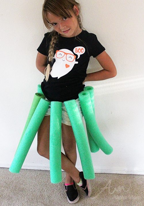 "Girl wearing DIY octopus ""legs"" made from green pool noodles"