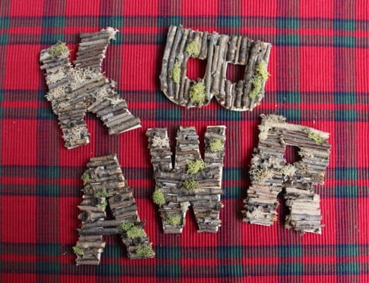 Letters made from pieces of stick laying on plaid table cloth