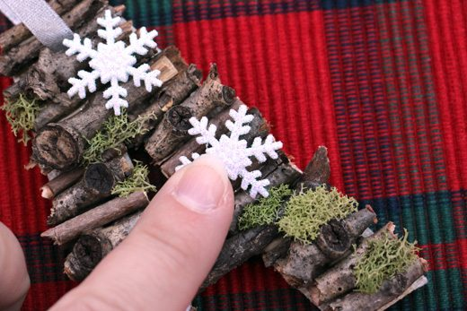 Decorating stick letters with moss and tiny snowflakes