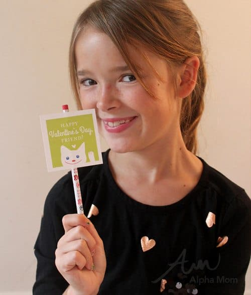 Child holding a green friendly valentines card attached to a pencil