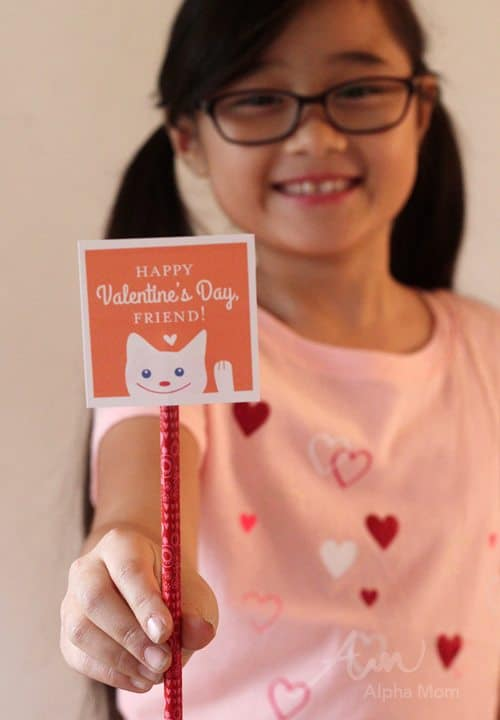 Child holding a orange friendly valentines card attached to a pencil