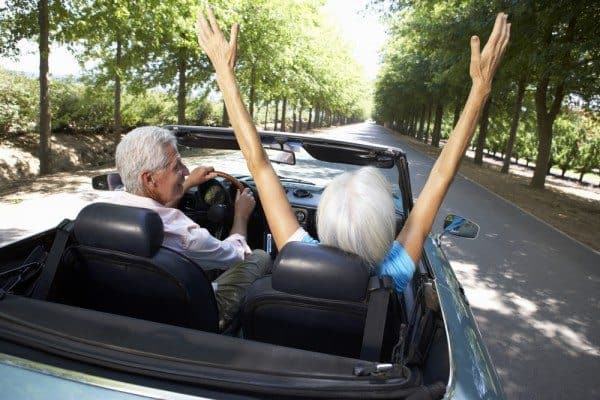 middle aged parents in a convertible with their mom's hands in the air