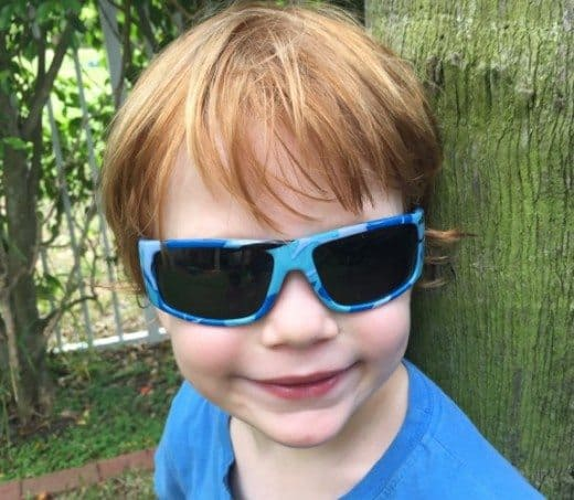 A young boy leaning on a tree wearing blue Junior Banz Sunglasse