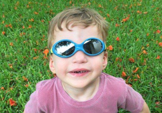 A boy wearing blue Julbo Looping 3 Sunglasses
