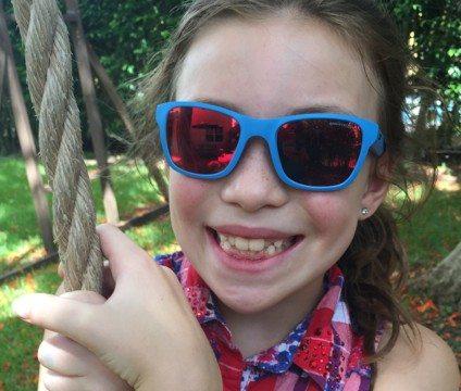 A girl wearing blue Julbo Reach Sunglasses