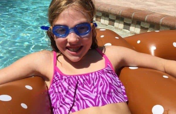 A tween girl floating in a pool, wearing swim googles