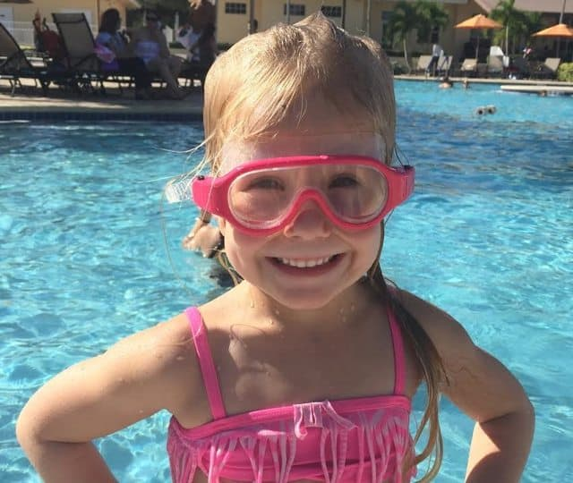A young girl in a swimming pool wearing a Babiators Submariners Swim Mask