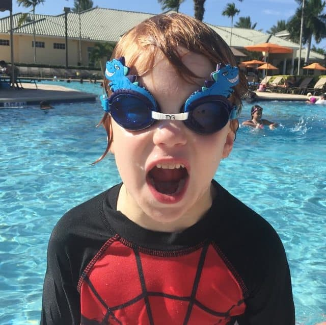 A young boy in a swimming pool wearing TYR Kids Swim Goggles