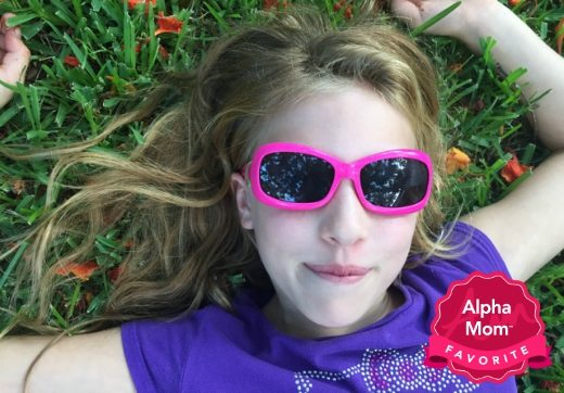 A girl laying in the glass wearing pink Real Kids Breeze Sunglasses